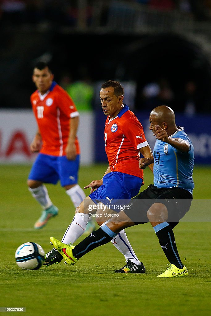 Marcelo Diaz of Chile (L) fights for the ball with Egidio Arevalo of Uruguay (R) during an international friendly match between Chile and Uruguay at Monumental Stadium on November 18 2014 in Santiago, Chile.