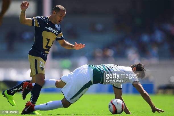 Marcelo Diaz of Pumas struggles for the ball with Nestor Araujo of Santos Laguna during the 16th round match between Pumas UNAM and Santos Laguna as...