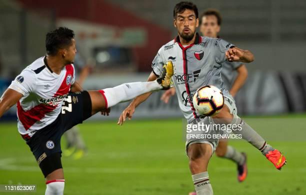 Marcelo Estigarribia of Argentina's Colon de Santa Fe vies for the ball with Yordi Vilchez of Peru's Deportivo Municipal during their Copa...