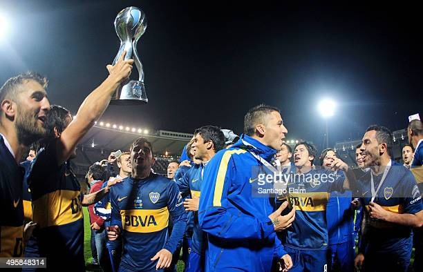 Marcelo Meli of Boca Juniors lifts the trophy as he celebrates with his teammates after winning a final match between Boca Juniors and Rosario...