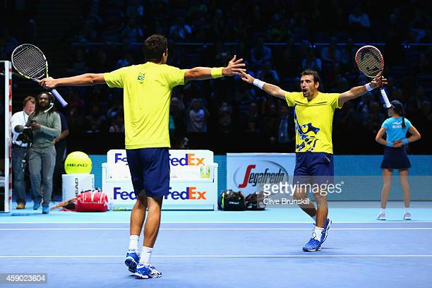 Marcelo Melo of Brazil and Ivan Dodig of Croatia celebrate match point in the doubles semifinal match against Lukasz Kubot of Poland and Robert...