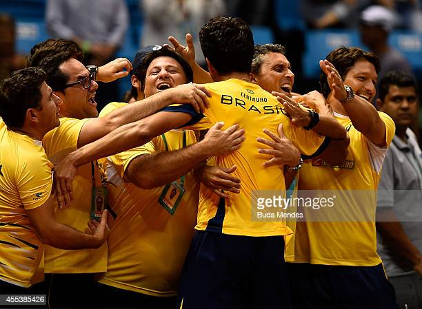 Marcelo Melo of Brazil celebrates victory with team members after his playoff doubles match against Marc Lopez and David Marrero of Spain on Day Two...