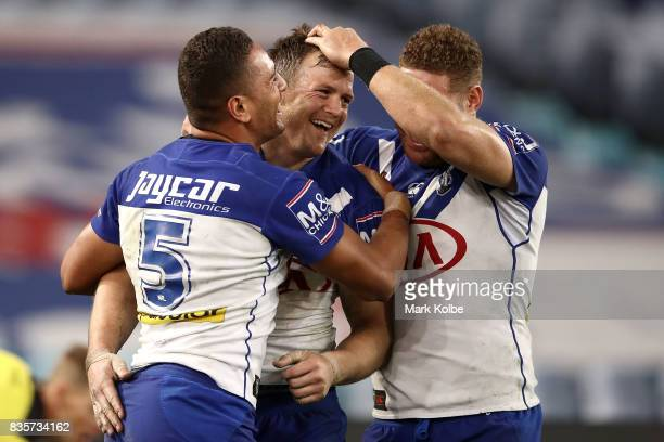 Marcelo Montoya Brett Morris and Brenko Lee of the Bulldogs celebrate Brett Morris scoring a try during the round 24 NRL match between the Canterbury...