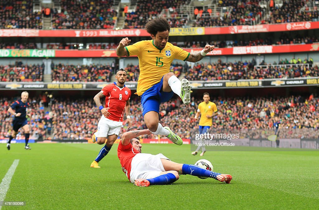 Marcelo of Brazil hurdles a sliding tackle from Mauricio Isla of Chile during the international friendly match between Brazil and Chile at the Emirates Stadium on March 29, 2015 in London,