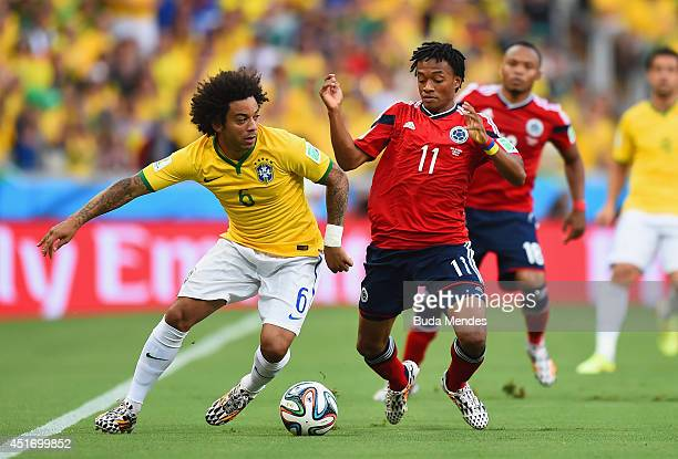Marcelo of Brazil is challenged by Juan Guillermo Cuadrado of Colombia during the 2014 FIFA World Cup Brazil Quarter Final match between Brazil and...