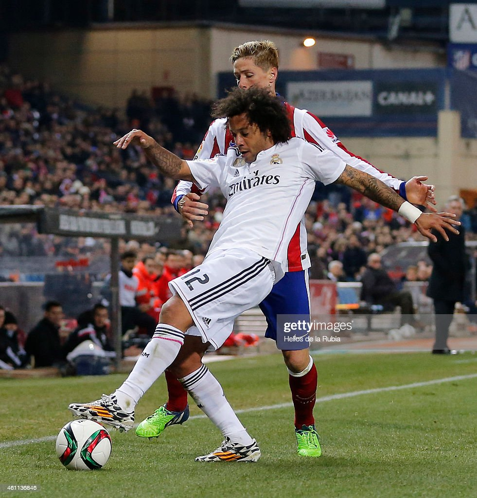 Marcelo (R) of Real Madrid and Fernando Torres of Atletico de Madrid compete for the ball during the Copa del Rey, round of 16 first leg match between Club Atletico de Madrid and Real Madrid CF at Vicente Calderon Stadium on January 7, 2015 in Madrid, Spain.