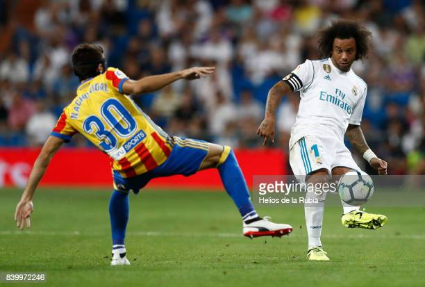 Marcelo of Real Madrid and Nacho Vidal of Valencia cf compete for the ball during the La Liga match between Real Madrid and Valencia CF at Estadio...