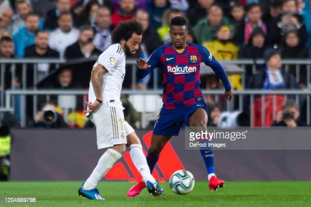 Marcelo of Real Madrid and Nelson Semedo of FC Barcelona battle for the ball during the Liga match between Real Madrid CF and FC Barcelona at Estadio...