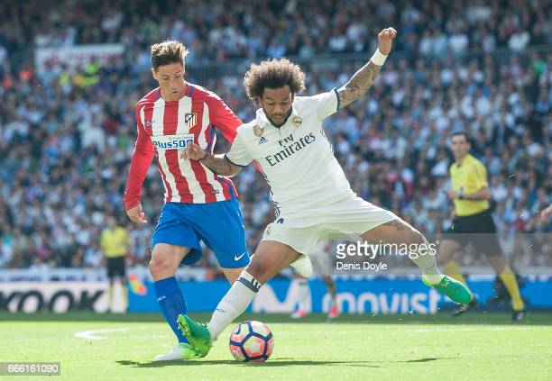 Marcelo of Real Madrid blocks Fernando Torres of Club Atletico de Madrid during the La Liga match between Real Madrid CF and Club Atletico de Madrid...