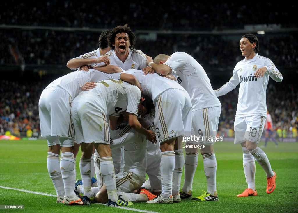 Marcelo of Real Madrid celebrates with team-mates after Cristiano Ronaldo (C) scored his team's second goal during the La Liga match between Real Madrid CF and Real Sporting de Gijon at Estadio Santiago Bernabeu on April 14, 2012 in Madrid, Spain.