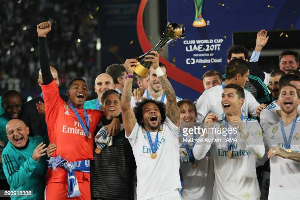 Marcelo of Real Madrid celebrates with the trophy and his teammates at the end of the FIFA Club World Cup UAE 2017 final match between Gremio and...
