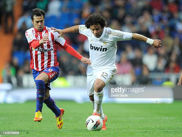 Marcelo of Real Madrid CF battles for the ball against Miguel Angel de las Cuevas of Real Sporting de Gijon during the La Liga match between Real...