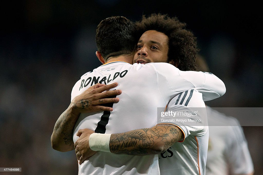 Marcelo of Real Madrid CF celebrates scoring their second goal with teammate Cristiano Ronaldo during the La Liga match between Real Madrid CF and Levante UD at Estadio Satiago Bernabeu on March 9, 2014 in Madrid, Spain.