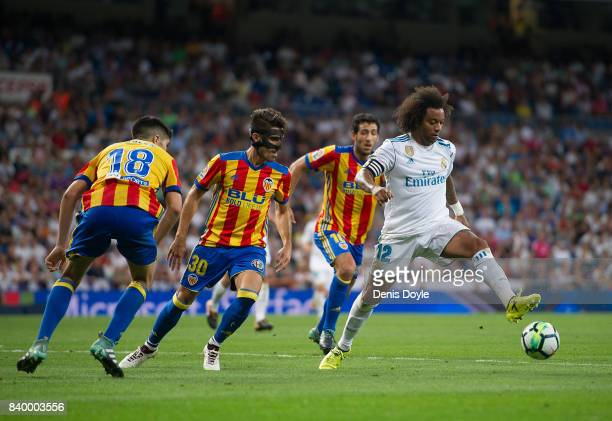 Marcelo of Real Madrid CF controls the ball beside Nacho Vidal of Valencia CFduring the La Liga match between Real Madrid CF and Valencia CF at...