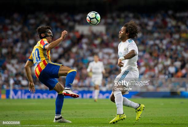 Marcelo of Real Madrid CF is challenged by Nacho Vidal of Valencia CF during the La Liga match between Real Madrid CF and Valencia CF at Estadio...