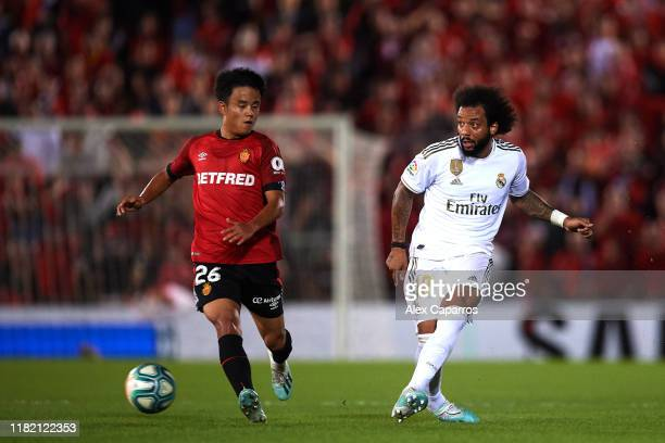 Marcelo of Real Madrid CF plays the ball under pressure from Takefusa Kubo of RCD Mallorca during the La Liga match between RCD Mallorca and Real...