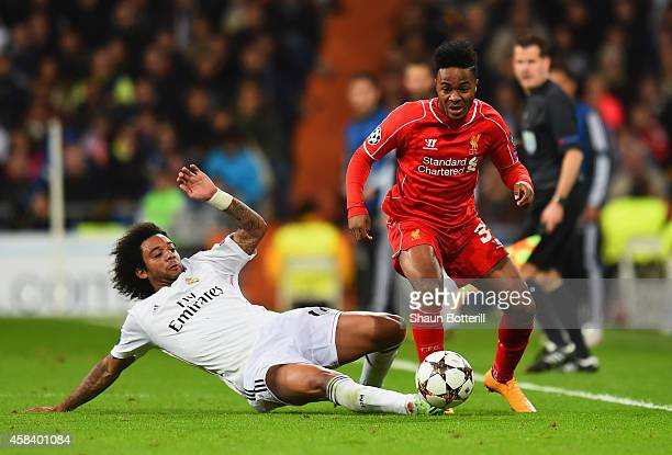 Marcelo of Real Madrid CF tackles Raheem Sterling of Liverpool during the UEFA Champions League Group B match between Real Madrid CF and Liverpool FC...