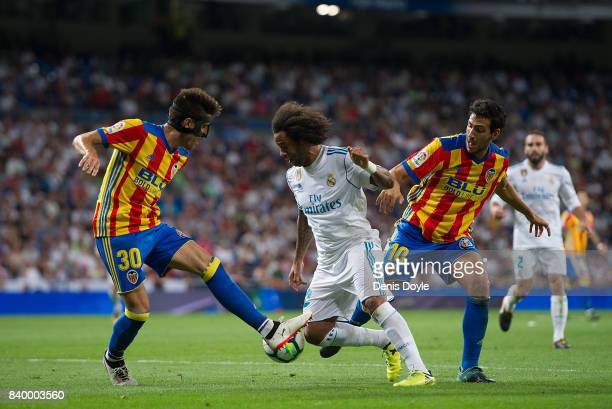 Marcelo of Real Madrid CF tries to get past Nacho Vidal and Daniel Parejo of Valencia CF during the La Liga match between Real Madrid CF and Valencia...