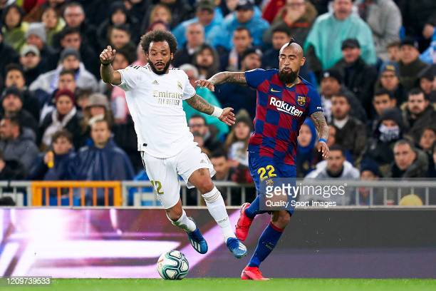 Marcelo of Real Madrid competes for the ball with Arturo Vidal of FC Barcelona during the Liga match between Real Madrid CF and FC Barcelona at...