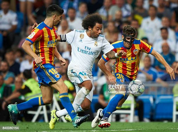 Marcelo of Real Madrid competes for the ball with Lato and Nacho Vidal of Valencia during the La Liga match between Real Madrid and Valencia at...