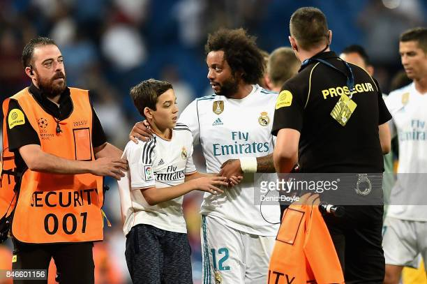 Marcelo of Real Madrid embraces a pitch invador after the UEFA Champions League group H match between Real Madrid and APOEL Nikosia at Estadio...
