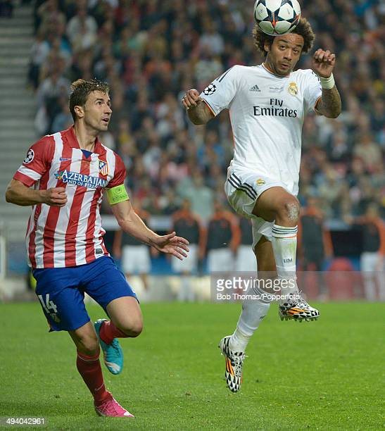 Marcelo of Real Madrid heads the ball watched by Gabi of Atletico de Madrid during the UEFA Champions League Final between Real Madrid and Atletico...