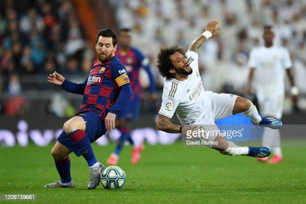Marcelo of Real Madrid is brought down by Lionel Messi of FC Barcelona during the Liga match between Real Madrid CF and FC Barcelona at Estadio...