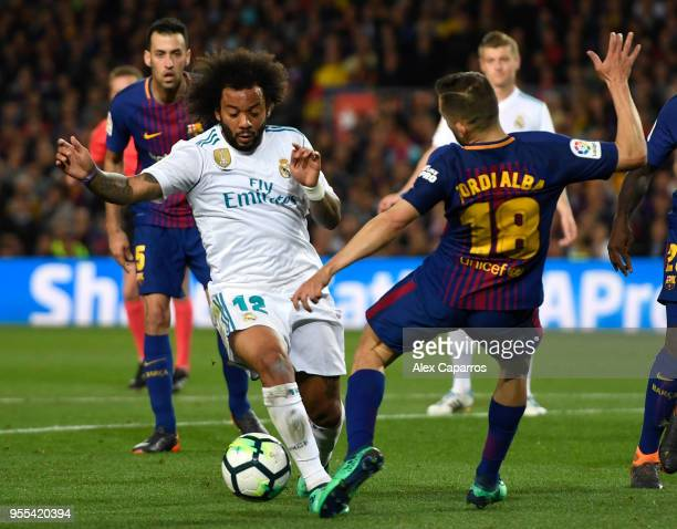 Marcelo of Real Madrid is challenged by Jordi Alba of Barcelona in the penalty area during the La Liga match between Barcelona and Real Madrid at...