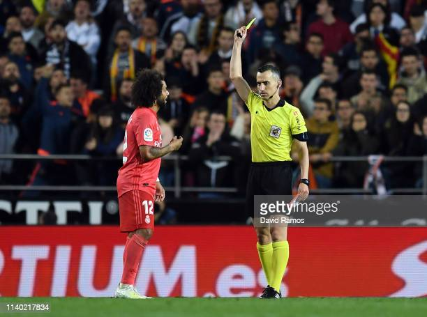 Marcelo of Real Madrid is shown a yellow card by Referee Jaime Latre during the La Liga match between Valencia CF and Real Madrid CF at Estadio...