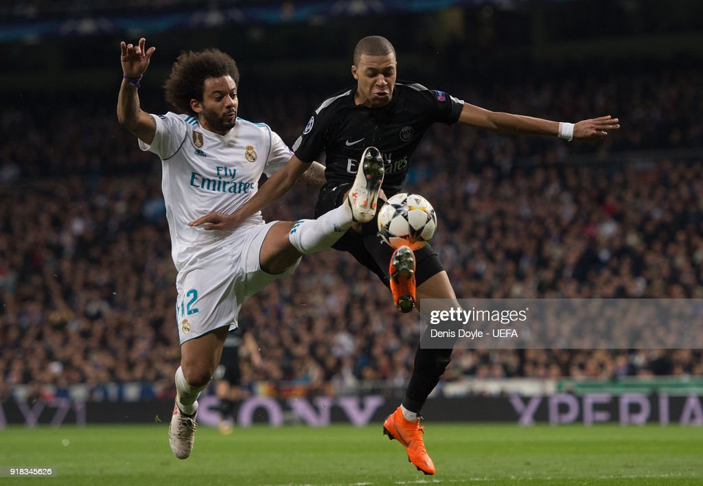 Marcelo of Real Madrid tackles Kylian Mbappe of Paris Saint-Germain during the UEFA Champions League Round of 16 First Leg match between Real Madrid and Paris Saint-Germain at Bernabeu on February 14, 2018 in Madrid, Spain.