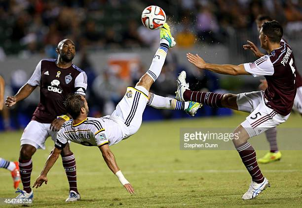 Marcelo Sarvas of the Los Angeles Galaxy gets off a shot with a bicycle kick between Marvell Wynne and Thomas Piermayr of the Colorado Rapids at...