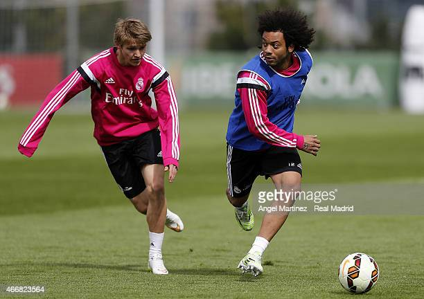 Marcelo Vieira and Martin Odegaard of Real Madrid in action during a training session at Valdebebas training ground on March 19 2015 in Madrid Spain