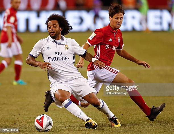 Marcelo Vieira Da Silva of Real Madrid drives by Fabian Benko of Bayern Munich during their International Champions Cup match at MetLife Stadium on...