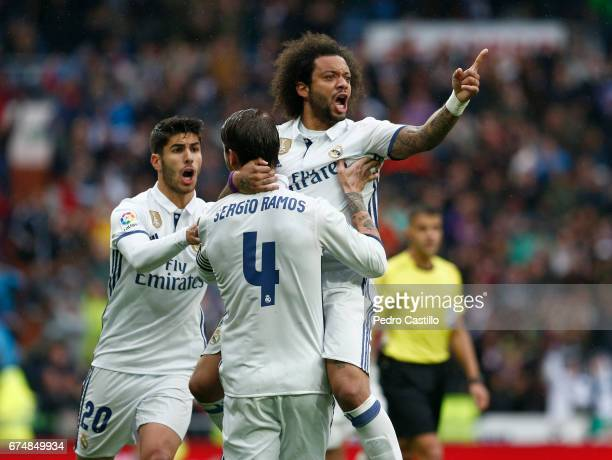 Marcelo Vieira of Real Madrid celebrates after scoring with his teammates Sergio Ramos and Marco Asensio during the La Liga match between Real Madrid...