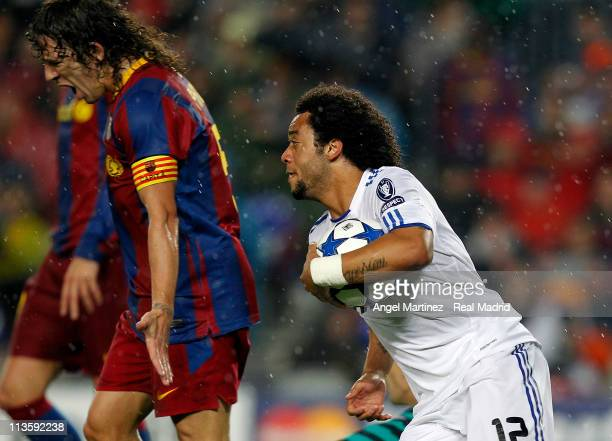Marcelo Vieira of Real Madrid celebrates beside Carles Puyol of Barcelona after scoring his side equalizer goal during the UEFA Champions League Semi...