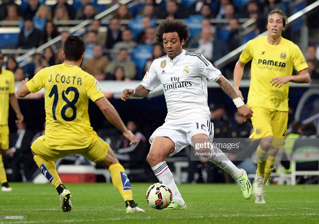 Marcelo Vieira (C) of Real Madrid is in action against Costa of Villarreal during the La Liga match between Real Madrid and Villarreal at Estadio Santiago Bernabeu in Madrid, Spain on March 1, 2015.