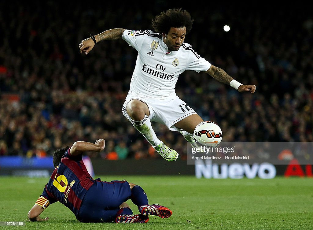 Marcelo Vieira of Real Madrid jumps over Xavi Hernandez of FC Barcelona during the La Liga match between FC Barcelona and Real Madrid CF at Camp Nou on March 22, 2015 in Barcelona, Spain.