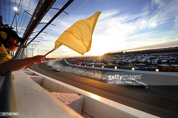 Flagger waves the caution flag as Jimmie Johnson Hendrick Motorsports Chevrolet Impala SS, drives by with smoke coming from his car after hitting the...