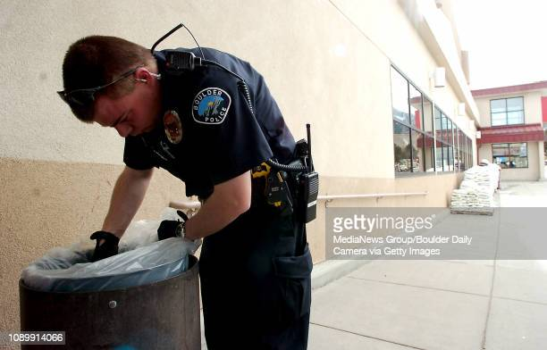 March 02 2006 A Boulder police office looks in a trash can outside of King Soopers on Table Mesa Thursday afternoon after the 1st Bank inside of King...