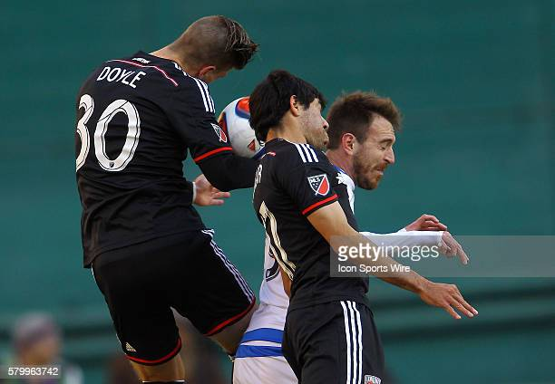Miguel Aguilar and Conor Doyle of DC United go up for a header against Eric Alexander of Montreal Impact during a MLS soccer match at RFK Stadium in...