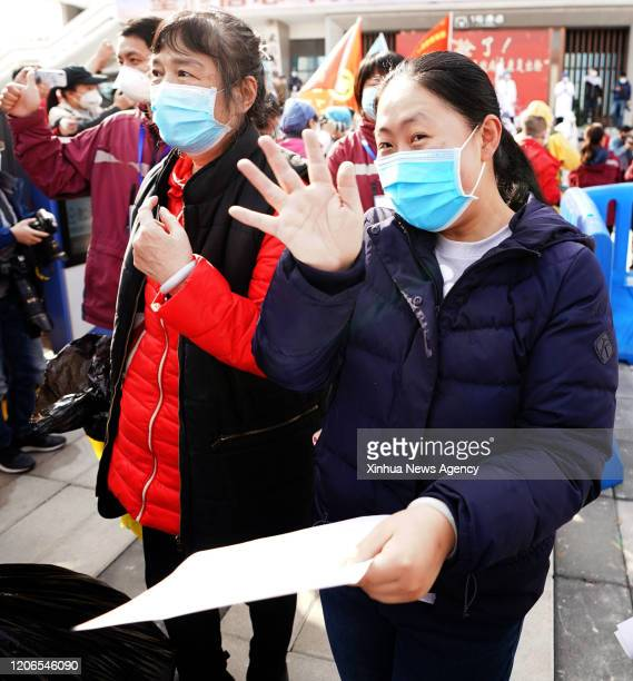 WUHAN March 10 2020 Cured coronavirus patients greet people after leaving the Wuchang temporary hospital in Wuhan central China's Hubei Province...