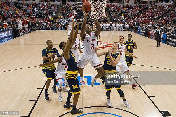 Indiana Hoosiers forward OG Anunoby scores in between Michigan Wolverines guard Zak Irvin and Michigan Wolverines guard Duncan Robinson during the...