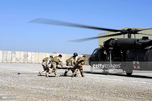 march 12, 2009 - soldiers rush a simulated casualty to a uh-60 blackhawk helicopter during an air assault and medical evacuation training on camp echo, iraq. the soldiers train constantly to maintain their combat readiness.  - evacuation stock pictures, royalty-free photos & images