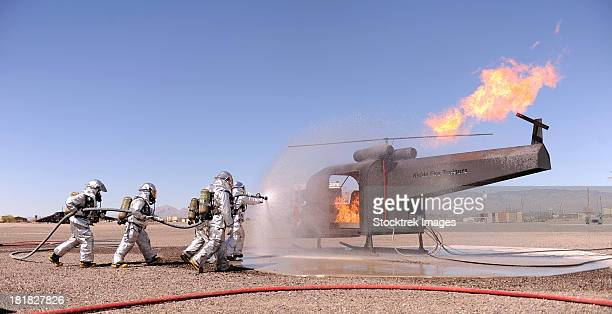 march 13, 2013 - u.s. air force airmen extinguish a fire as part of their training during the operational readiness exercise on davis-monthan air force base, arizona.  - fire protection suit stock pictures, royalty-free photos & images