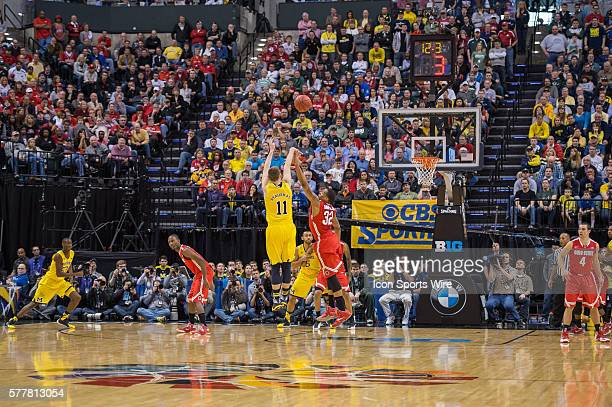 Michigan Wolverines guard Nik Stauskas shoots a three pointer over Ohio State Buckeyes guard Lenzelle Smith Jr as the shot clocks runs down during...