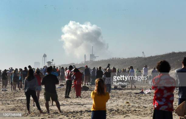 March 15, 2020 - Titusville, Florida, United States - People watch from Playalinda Beach at Canaveral National Seashore as a cloud of smoke forms...