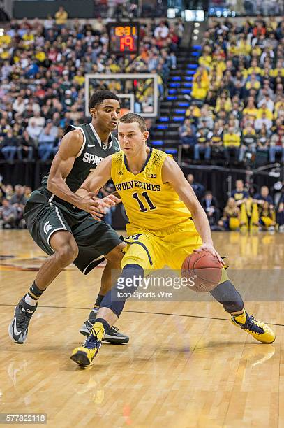 Michigan Wolverines guard Nik Stauskas dribbles by Michigan State Spartans guard Gary Harris during the Big Ten Men's Basketball Tournament...