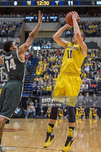 Michigan Wolverines guard Nik Stauskas shoots over Michigan State Spartans guard Gary Harris during the Big Ten Men's Basketball Tournament...
