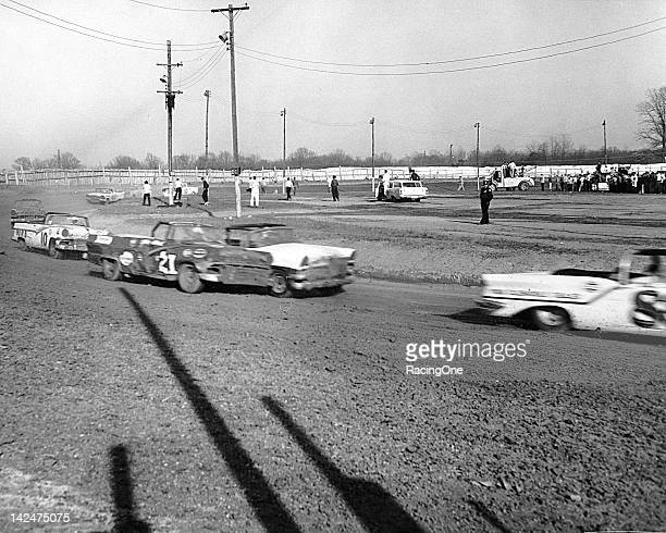 Glen Wood in a Ford races sidebyside with the Mercury of Billy Myers as the pair chase Bill Lutz during a NASCAR Convertible Series race at...
