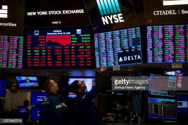 NEW YORK March 18 2020 Traders work on the floor of the New York Stock Exchange in New York the United States March 18 2020 US equities ended...